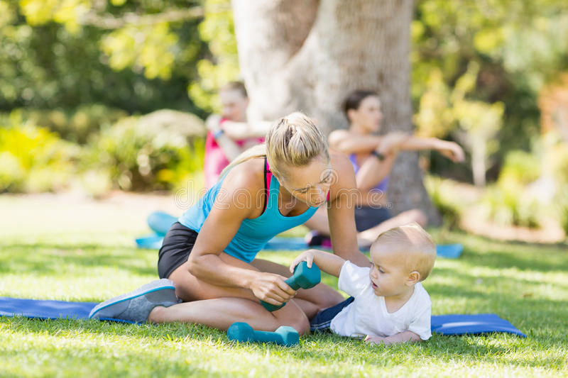 Woman with her baby while exercising. In park royalty free stock image