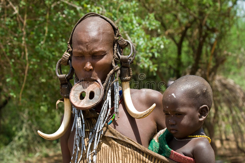 Woman with her baby of the Mursi tribe. royalty free stock photo