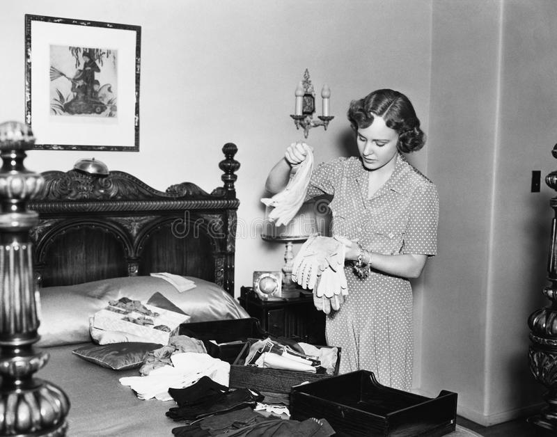 Woman in her bedroom sorting her gloves royalty free stock photography