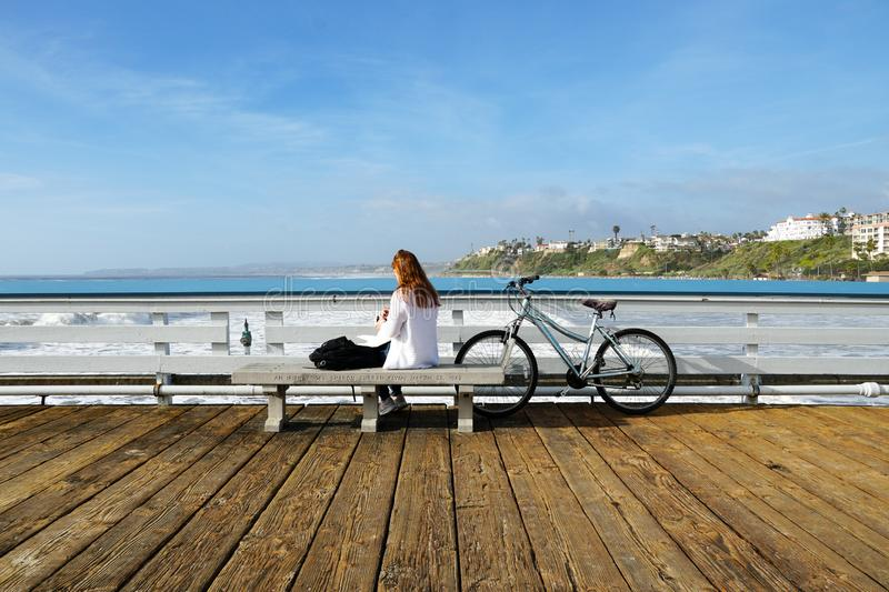Woman with her bike on San Clemente Pier. Reading a book and  looking at the view royalty free stock photo