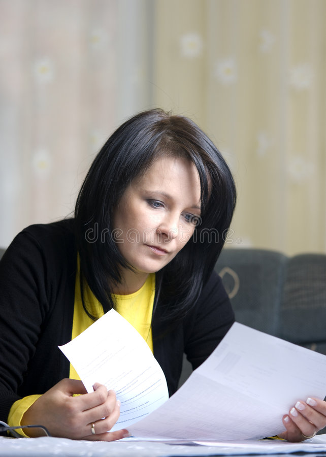 Woman and her bills. A brunette woman sitting at the living room table, looking with concern at her monthly bills to pay. Easy to crop composition royalty free stock photography