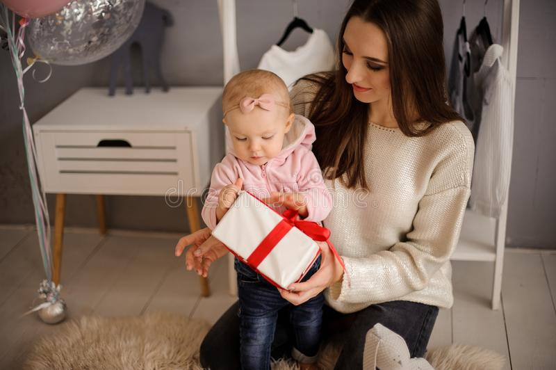 Woman and her cute little daughter holding a present royalty free stock photo