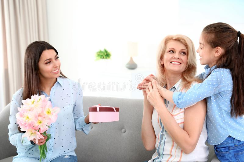 Woman and her daughter congratulating granny. Happy Mother`s Day stock photo