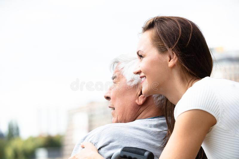 Woman With Her Disabled Father Near Railing stock photo