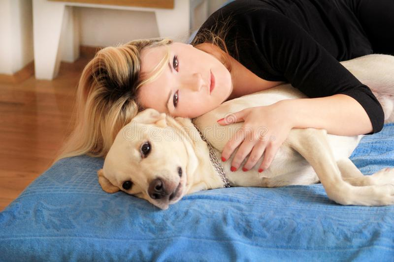 Woman with her dog in bed at home, relaxing in bedroom. Beautiful girl is playing, together and petting with dog in bed. royalty free stock photography