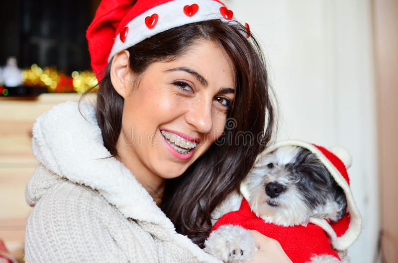 Woman with her dog with red christmas hats. Beautiful woman hugging her dressed white dog with red christmas hats stock images