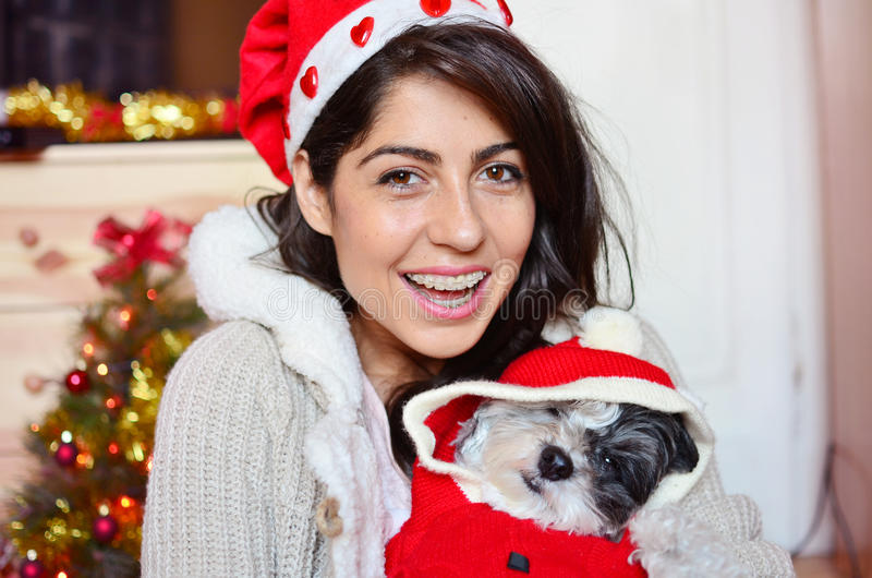 Woman with her dog with red christmas hats. Beautiful woman hugging her dressed white dog with red christmas hats royalty free stock photo