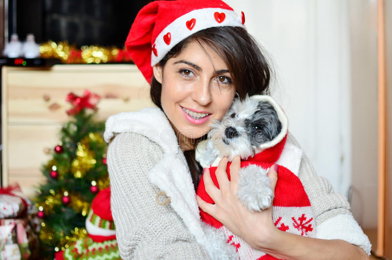 Woman with her dog with red christmas hats. Beautiful woman hugging her dressed white dog with red christmas hats royalty free stock images