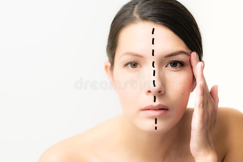Woman with her face divided to show aging stock photography