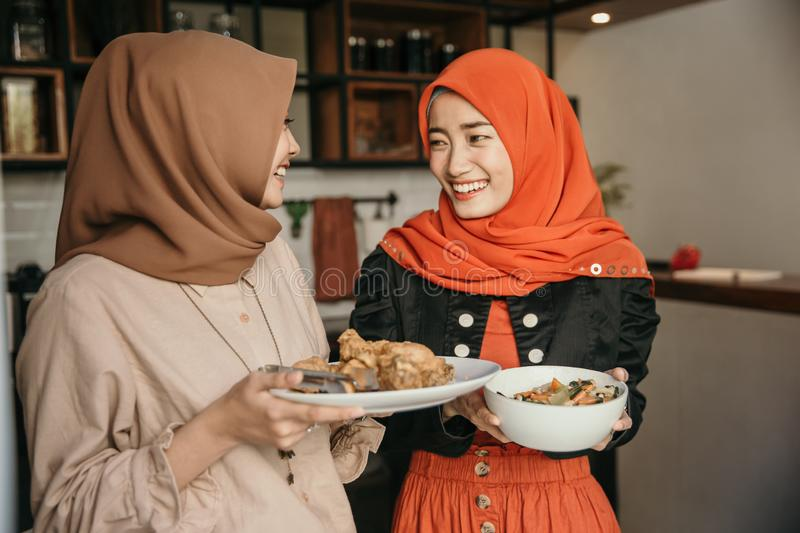 Woman and her friend preparing food for breaking fast. Happiness women and her friend preparing food for breaking fast at home stock photos