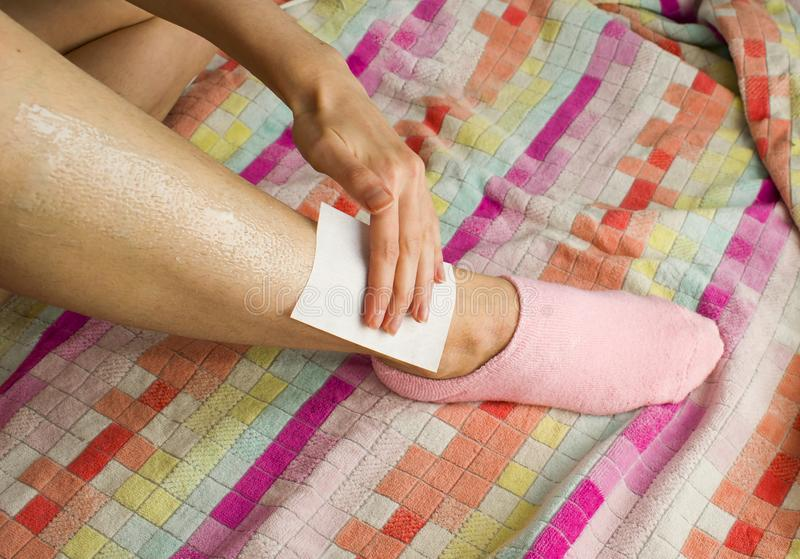 Woman and her hairy leg on a multi-colored towel. Girl in anticipation of procedures of depilation by wax. Woman and her hairy leg on multi-colored towel. Girl royalty free stock photos