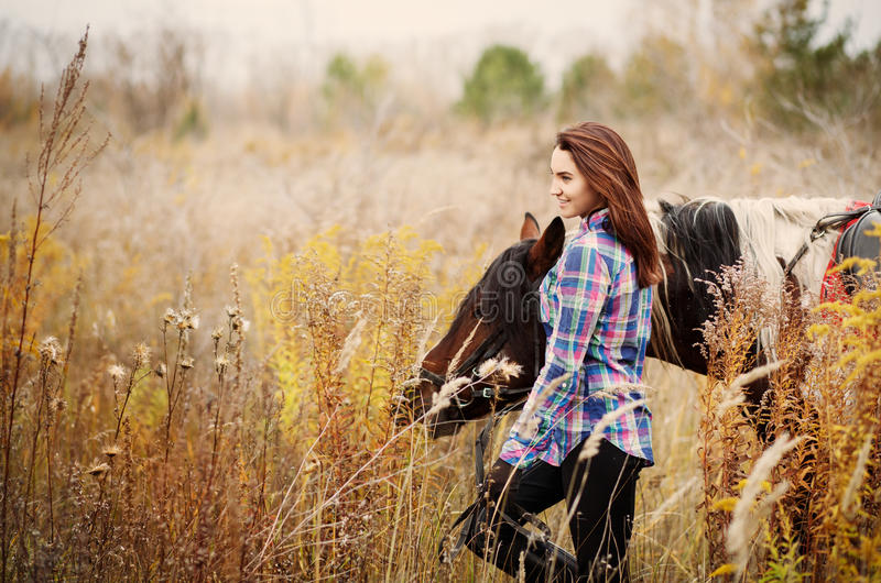 Woman and her horse outdoors. Brunette Woman and her horse outdoors. Lifestyle concept with copyspace stock images