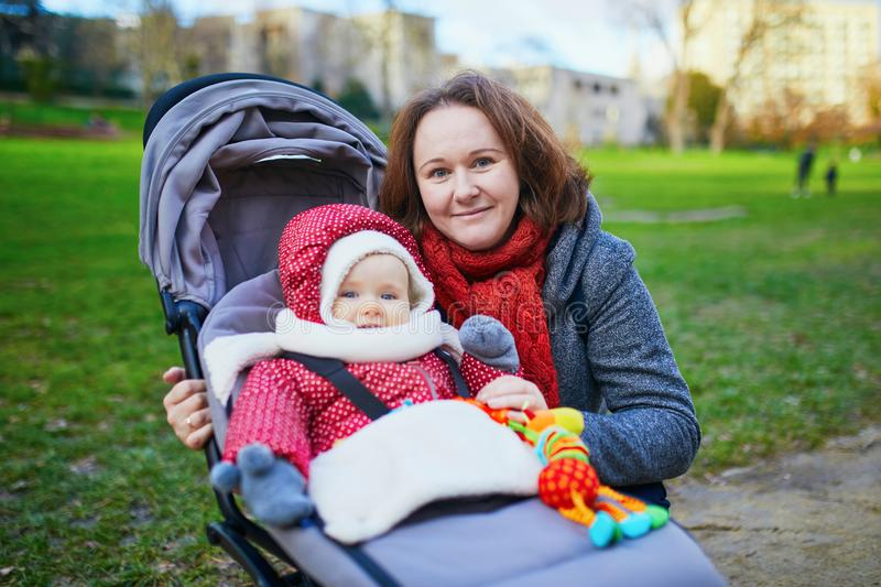 Woman with her little baby girl in stroller. Mother walking in park stock photo