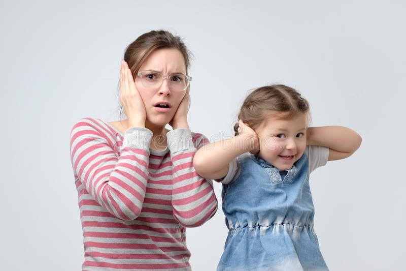 Woman and her little daughter cover ears with hands. Avoid loud noise. Beautiful young women and her little daughter cover ears with hands, trying to be hear stock photo
