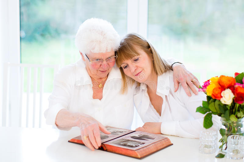 Woman and her mother watching black and white photo royalty free stock photos