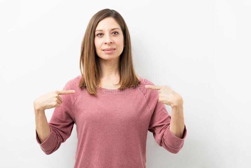 Woman in her 40s pointing at herself. Portrait of a beautiful woman in her 40s dressed casual and pointing at herself in a studio stock photo