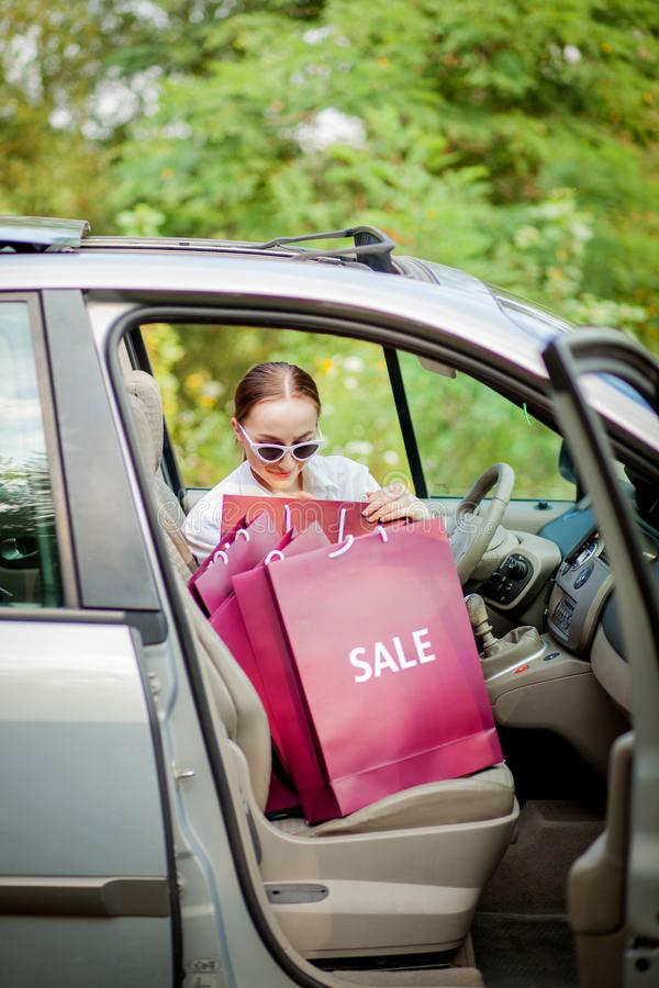 Woman with her shopping bags into the car - shopping concept royalty free stock photo