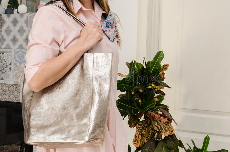 Woman on her shoulder has a large capacious pearly fashion bag. Trendy large bag with a metallic glow stock photo