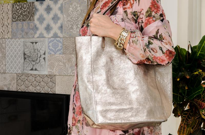 Woman on her shoulder has a large capacious pearly fashion bag. Trendy large bag with a metallic glow stock images