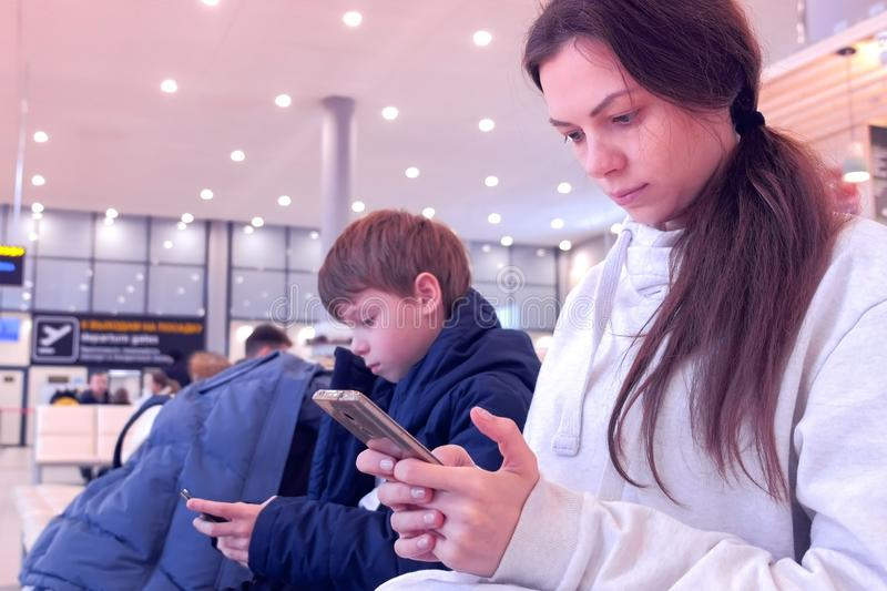 Woman with her son browsing on mobile phones in airport hall waiting for flight. stock photo