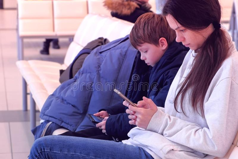 Woman with her son browsing on mobile phones in airport hall waiting for flight. Side view. royalty free stock photos