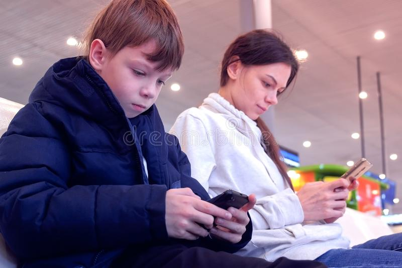 Woman with her son browsing on mobile phones in airport hall waiting for flight. royalty free stock photo