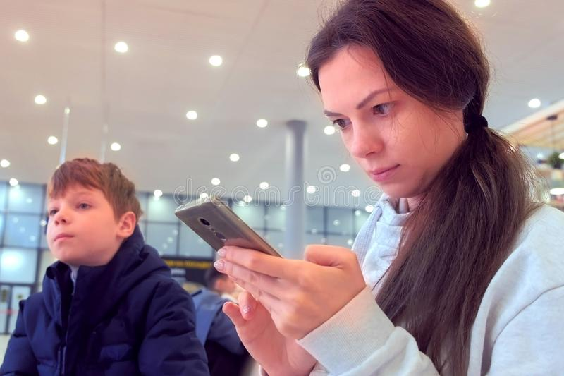 Woman with her son check-in online registration on her mobile phone in airport hall. royalty free stock images
