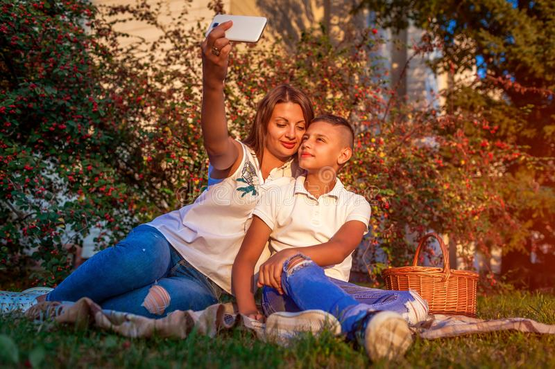 Woman with her teenager son taking selfie on smartphone. Happy family spending time outdoors sittting on grass in park. royalty free stock image