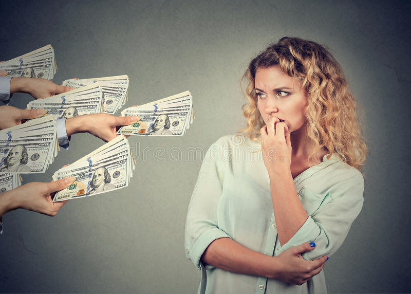 Woman hesitant to take bribe from people. Young woman hesitant to take bribe from people royalty free stock image
