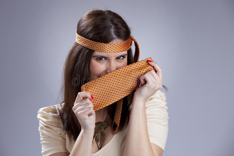 Woman hidding behind a necktie. Happy young woman hiding behind a necktie royalty free stock photo
