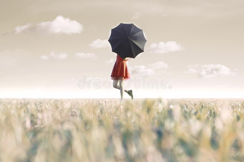 Woman hides behind his black umbrella in a surreal place stock images