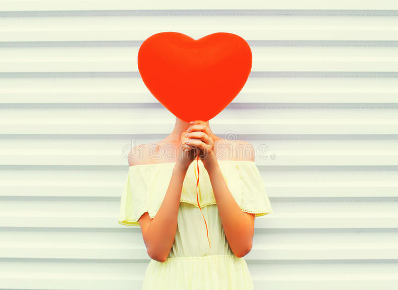 Woman hides head red air balloon heart shape over white stock images