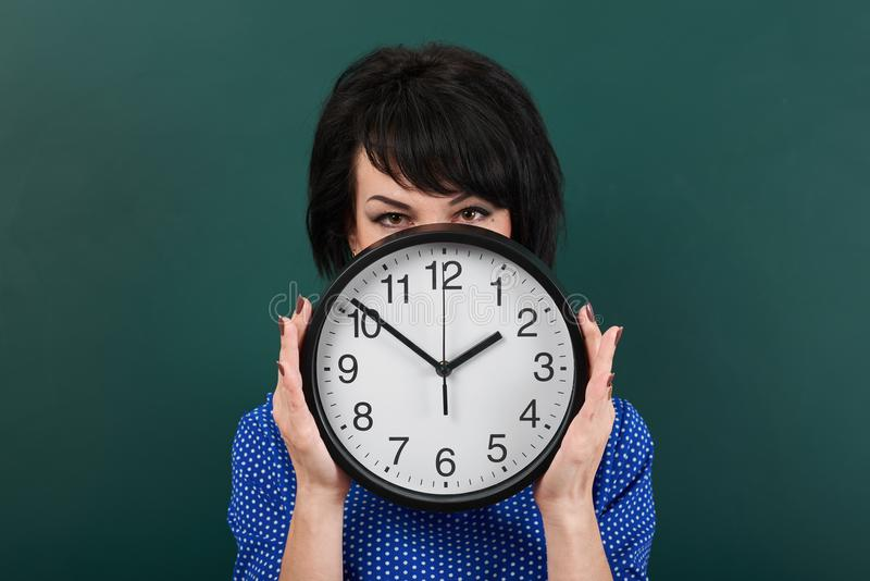 Woman hides her face behind the clock, posing by chalk board, time and education concept, green background, studio shot stock photo