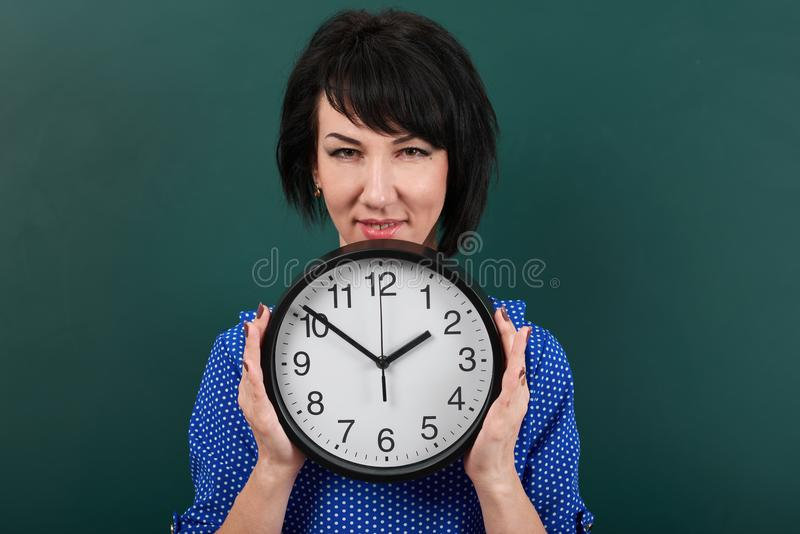 Woman hides her face behind the clock, posing by chalk board, time and education concept, green background, studio shot stock images
