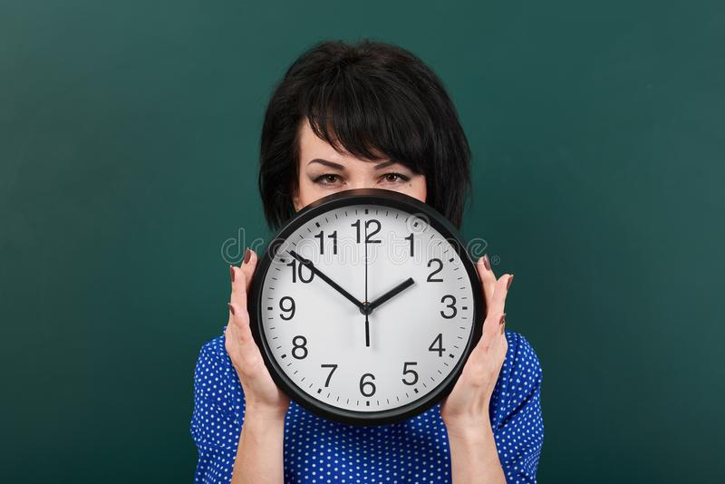 Woman hides her face behind the clock, posing by chalk board, time and education concept, green background, studio shot royalty free stock photography