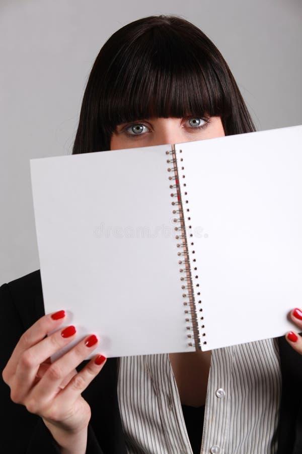 Woman hiding behind notebook stock photos