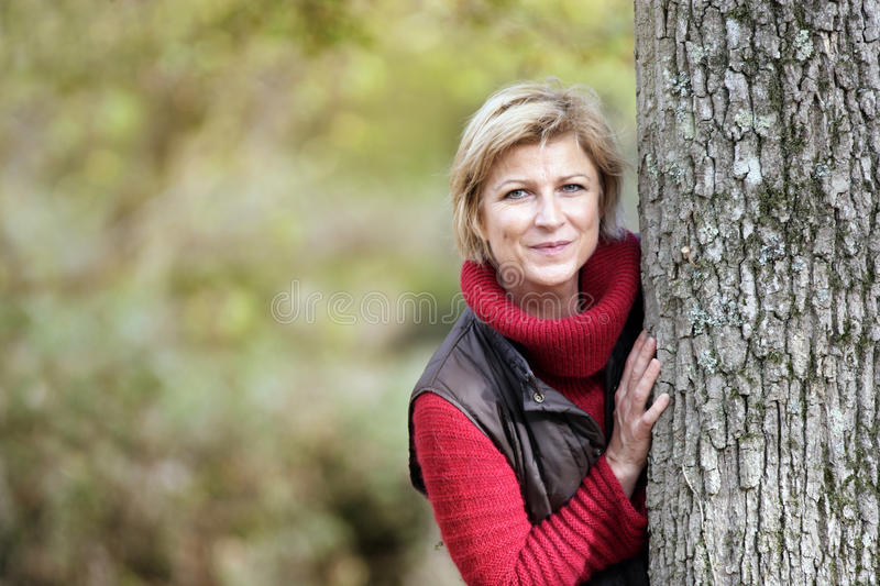 Woman hiding behind a tree stock images