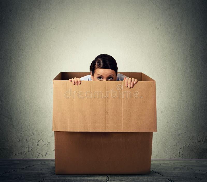 Woman hiding in a carton box. Young woman hiding in a carton box stock images