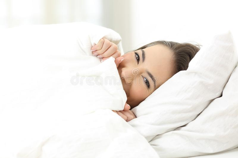 Woman hiding face on the bed stock photography