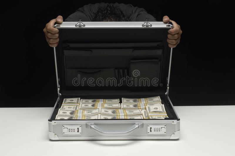 Woman Hiding Face Behind Suitcase Full Of Dollars