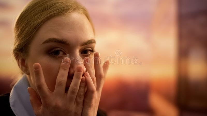 Woman hiding face in hands, shocked with bad news, feeling desperate, closeup stock photography