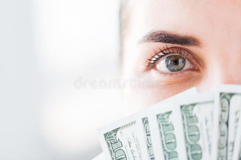 Woman hiding her face behind us dollar money fan royalty free stock images