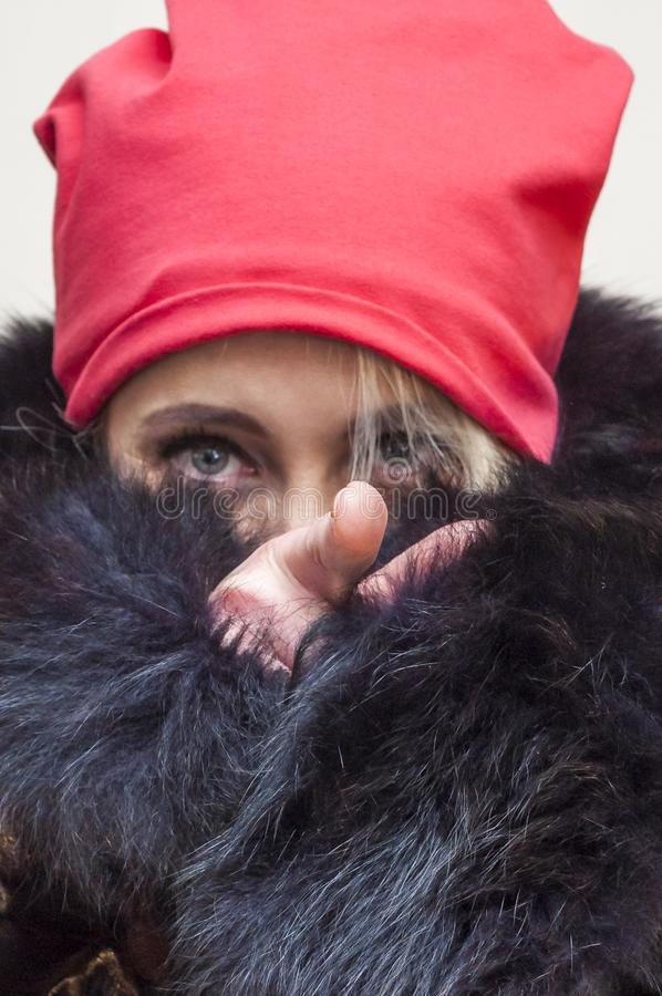 Woman hiding her face under fur coat and pointing on camera with finger stock image
