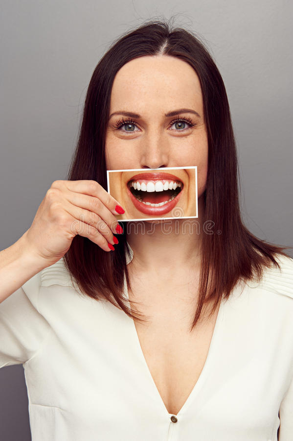 Woman hiding her true emotions in the smile royalty free stock image