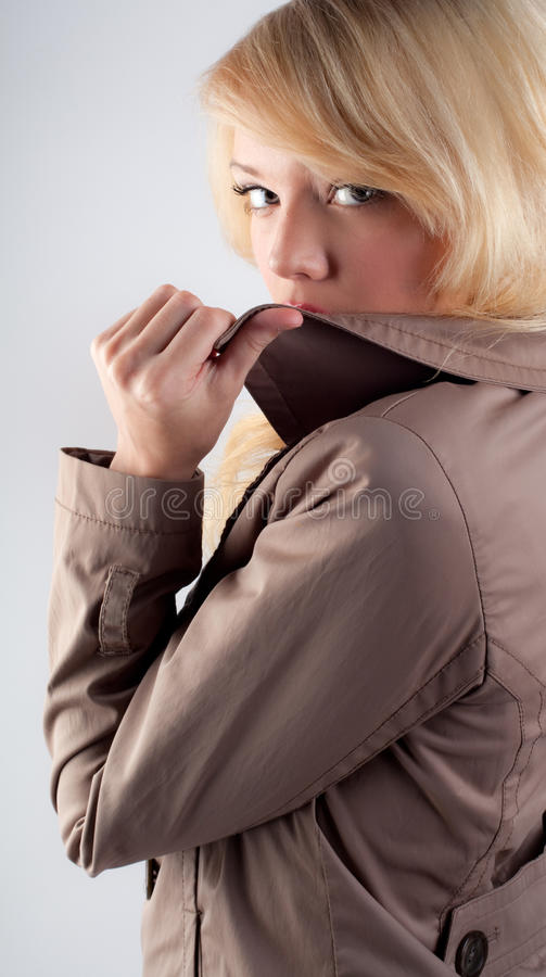 Woman Hiding Lips Behind Jacket Collar stock images