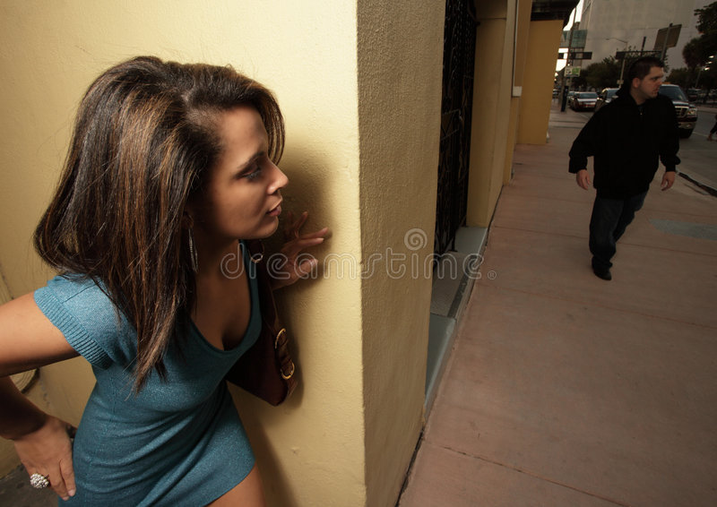 Woman hiding from the stalker. Young woman hiding behind a wall so the stalker wont see her royalty free stock photography