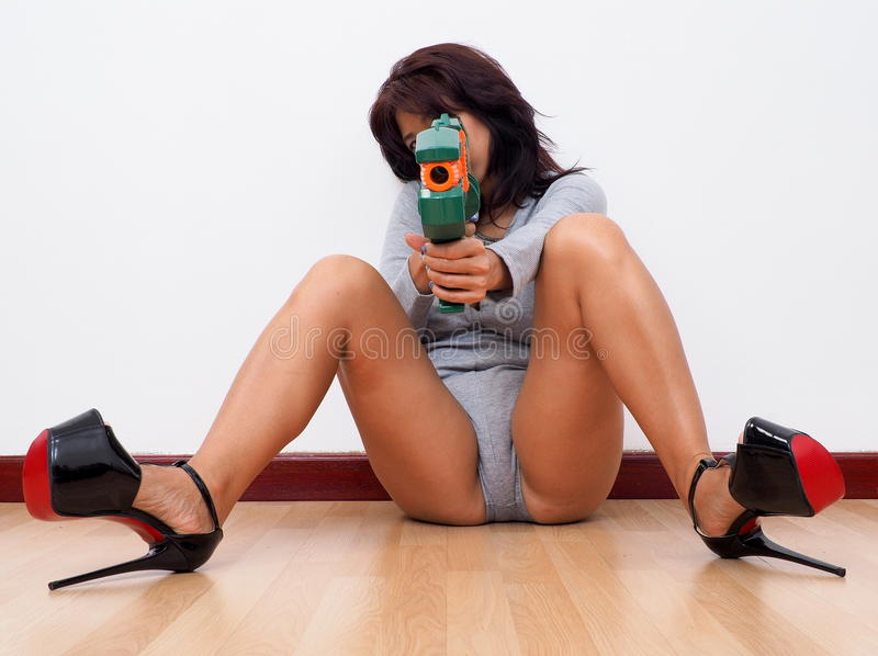 Woman with high heels aiming with toy gun. Woman sitting on the floor and wearing black high heel shoes and rompers aims at the camera with a toy gun stock photography