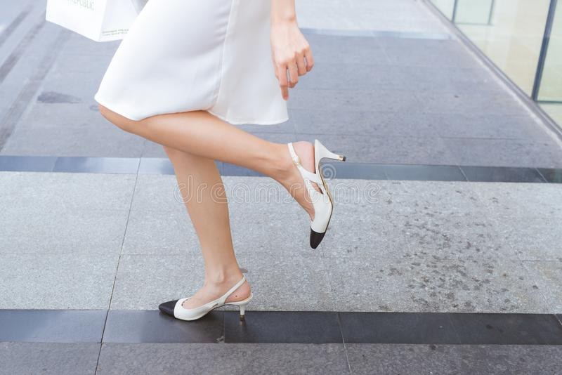 Woman on high heels has difficulties to walk in her shoes.  royalty free stock photography
