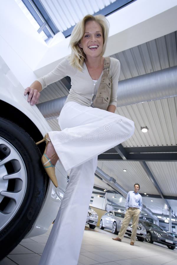 Woman in high heels leaning on new car stock photography