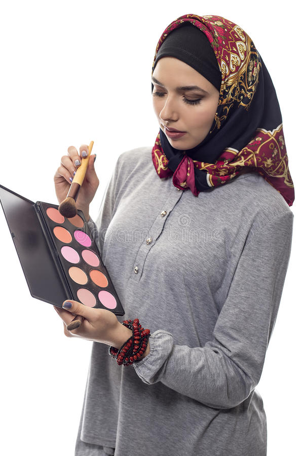 Woman in Hijab as a Make Up Artist. Female make up artist wearing a red hijab with a cosmetic palette to depict conservative fashion. The headscarf is associated royalty free stock photos